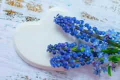Cora??o branco da porcelana e um ramalhete de flores azuis pequenas em um fundo claro de madeira Carro Wedding decorado foto de stock royalty free