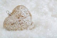 Cora??o de vidro em uma neve e fundo borrado tonificado da cor do bokeh de brilho com luzes de incandesc?ncia Decora??o do Natal  fotografia de stock