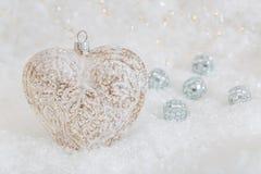 Cora??o de vidro em uma neve Fundo branco borrado do bokeh de brilho com luzes de incandesc?ncia Decora??o do Natal Bolas do espe imagens de stock royalty free