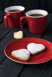 Corações vermelhos do copo e da cookie em um fundo preto Imagens de Stock