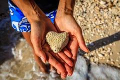Corail en forme de coeur dans des mains, île de Boracay, Philippines Photographie stock libre de droits