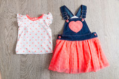 Corail et robe bleue, combinaisons avec le dessus sur le fond en bois gris Équipement de petite fille Vue Photo stock