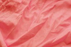 Coral background from a textile material with wicker pattern, closeup. Cloth backdrop. Crumpled fabric. Selective focus royalty free stock image