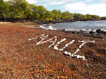 Coral Beach. A message spelled out in white coral left by a walker on a deserted black coral beach located on the south end of the Hawaiian island of Maui Royalty Free Stock Image