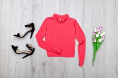 Coral blouse, black shoes, bouquet of tulips. Fashionable concept. Wooden background Royalty Free Stock Images
