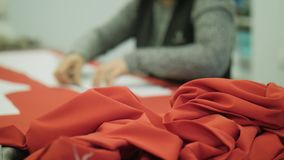 Coral cloth on the background of the dressmaker out of focus at work. Closeup background stock video
