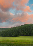 Coral Clouds Above Peaceful Green Field Stock Photo