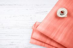 Coral color yoga mat and belt on white wooden background with copy space. Coral color exercise yoga mat and white belt on white wooden background with copy stock image