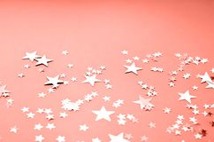 A coral colored background with many shiny stars stock photos
