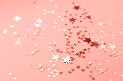 A coral colored background with many shiny stars stock image