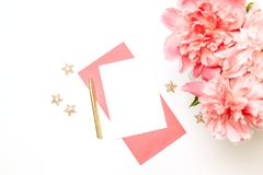 Coral composition made of pink paper envelope with a gold pen, a bouquet of coral peonies isolated on white background. Creative coral composition made of pink royalty free stock images