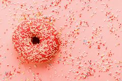 Coral donut lying on pink. Donut decorated with icing on pink stock photos