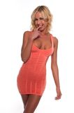 Coral dress. Pretty young blonde woman in a coral pink dress stock photography