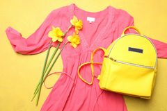 Coral dress, stylish yellow backpack and bouquet of  narcissus royalty free stock image