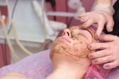 Coral face peeling. Cosmetician is applying facial mask. Organic cosmetics for delicate skin royalty free stock photography