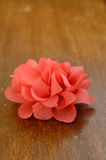 Coral flower brooch on brown table Stock Photography