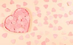 Coral heart-shaped box full of confetti hearts stock image
