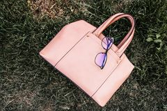 Coral leather female bag on the grass on the background of sky stock photos