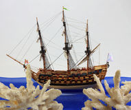 Coral and model of a sailing vessel. Two branches of a coral and model of a Royalty Free Stock Photography