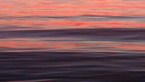 Coral orange reflection on  violet small smooth waves