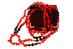 Coral red and black beads (necklace) and chest. Bright coral red and black beads (necklace) and crimson velvet box for jewelry (jewellery) on isolated Stock Image