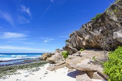 Coral reef and big granite rocks with palms at the beach of gran Stock Images