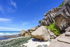 Coral reef and big granite rocks with palms at the beach of gran Royalty Free Stock Image