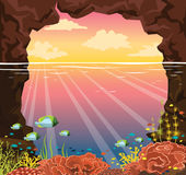 Coral reef, fish, underwater cave, sea, sunset sky. Stock Image