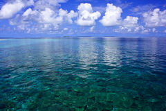 Coral reef near island. Deep blue ocean and clouds reflecting in the water Stock Photography