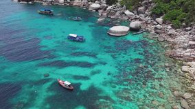 Coral Reef in Turquoise Lagoon Water beside Rocky Shoreline with Big Stones in Tropical Country. Aerial Top View. Shot with a DJI Mavic fps 29,97 4k stock footage