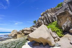 Coral reef and big granite rocks with palms at the beach of gran Royalty Free Stock Images