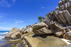 Coral reef and big granite rocks with palms at the beach of gran Royalty Free Stock Photography