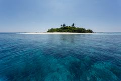 Coral reefs surrounding small tropical island Royalty Free Stock Photos