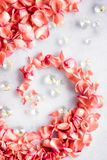 Coral rose petals on marble, color of the year - flower backgrounds and holidays concept. Coral rose petals on marble, color of the year - flower backgrounds and stock images