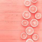 Coral toned oranges pattern. Creative scandinavian style flat lay top view of fresh orange fruit slices on coral wooden table background with copy space. Minimal stock photos