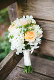 Coral White Bridesmaid Bouquet. Pink and coral peach roses in bridesmaid wedding bouquet leaning on a rustic wooden bench in the forest Royalty Free Stock Photos