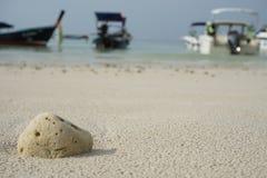 Corallo tirato sulla sabbia Abbia un'immagine della barca come fondo Immagine Stock Libera da Diritti
