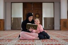 Corano musulmano della lettura del figlio e della donna, famiglia musulmana Immagine Stock