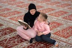 Corano musulmano della lettura del figlio e della donna, famiglia musulmana Fotografie Stock