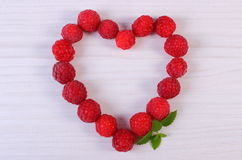 Coração de framboesas frescas na tabela de madeira branca, símbolo do amor Fotos de Stock Royalty Free