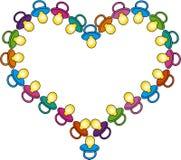 Coração de soothers coloridos do bebê Imagens de Stock