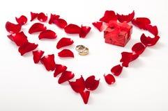 Coração feito das pétalas cor-de-rosa vermelhas e do anel dourado Fotos de Stock Royalty Free