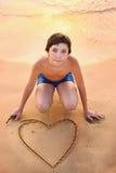 Corazón adolescente del dibujo del muchacho en la arena Imágenes de archivo libres de regalías