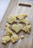 Corazón aislado de la pasta en una tabla de cortar Imagen de archivo