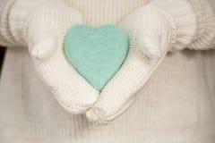 Corazón azul del día de tarjetas del día de San Valentín en manos con las manoplas de punto Fotografía de archivo