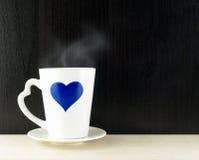Corazón azul en la taza de café en fondo de madera de la tabla Imagenes de archivo