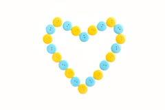 Corazón azul y amarillo del clasper plástico fotografía de archivo libre de regalías