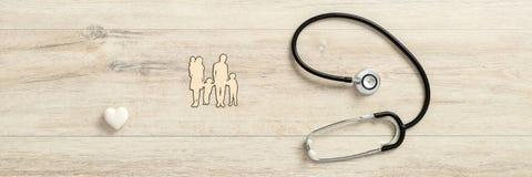 Corazón blanco con el estetoscopio médico al lado de una familia imagen de archivo libre de regalías