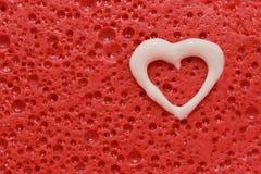 Corazón blanco en fondo rojo Imagenes de archivo
