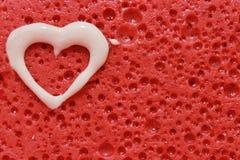 Corazón blanco en fondo rojo foto de archivo